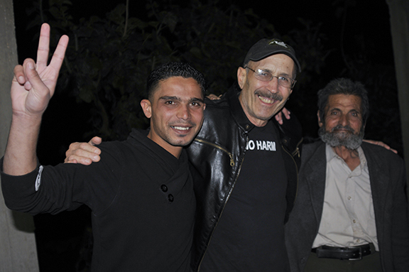 Taha's brother (left) and father (right) with Veteran For Peace member Tarak Kauff. Photo by ELLEN DAVIDSON