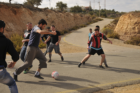Palestinians and Germans play a fierce football match; behind them, the road leads up to an illegal Israeli settlement. Photo by ELLEN DAVIDSON
