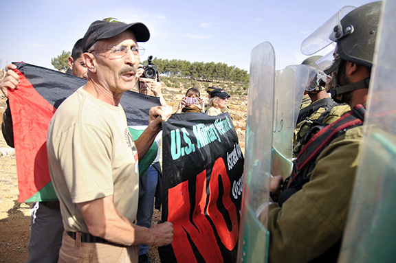 VFP Board Member speaks to Israeli soldiers as they push demonstrators back off the road. Photo by ELLEN DAVIDSON