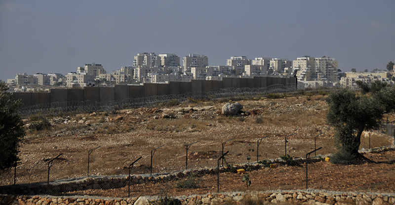 The wall divides the village of Bil'in from the settlement of Modi'in Illit, grabbing 60 percent of the village's agricultural lands in the process. Photo by ELLEN DAVIDSON