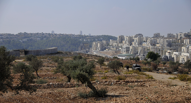 Israeli jeeps and troops guarding the wall. Behind them to the left is the hole where the gate used to be; to their right is the settlement of Modi'in Illit. Photo by ELLEN DAVIDSON