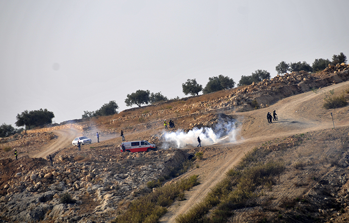 Israeli soldiers lob tear gas at a Palestinian ambulance. Photo by ELLEN DAVIDSON