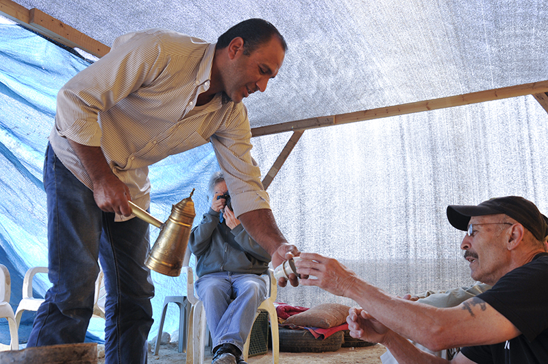 Aziz Al-Toury serves tea to Veterans For Peace member Tarak Kauff. Photo by ELLEN DAVIDSON