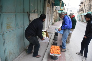 Setting up a makeshift vegetable stand on Hebron's Shuhada Street. PHOTO: ELLEN DAVIDSON