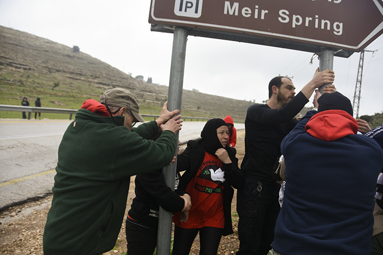 Shaking the sign for the spring, which Israeli settlers have claimed. PHOTO: ELLEN DAVIDSON