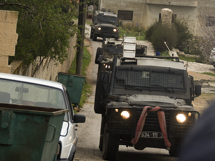 We go back to the village, and the soldiers come up the road to our host's house in jeeps. PHOTO: ELLEN DAVIDSON